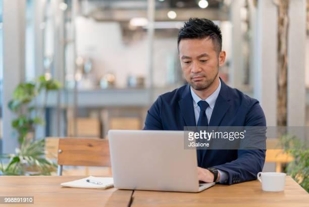 近代的なオフィスにラップトップを使用しての実業家 - 日本人のみ ストックフォトと画像