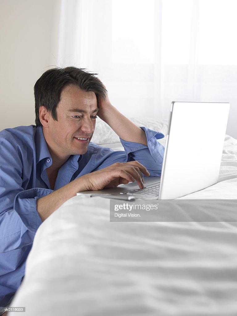 Businessman Using a Laptop on His Bed : Stock Photo