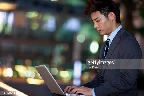 businessman using a laptop outside,night scene