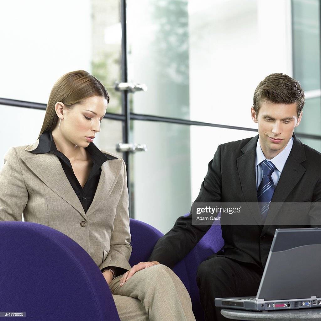 Businessman Using a Laptop Sits Next to a Businesswoman, Touching Her Leg and Smirking : Stock Photo