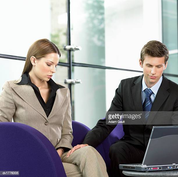 businessman using a laptop sits next to a businesswoman, touching her leg and smirking - man touching womans leg fotografías e imágenes de stock