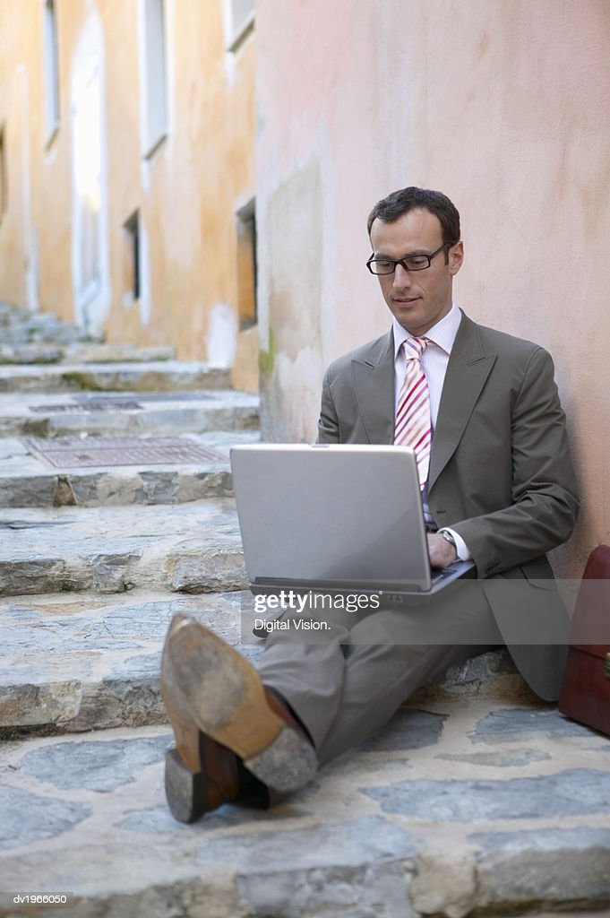 Businessman Using a Laptop Sitting on Steps on the Pavement : Stock Photo