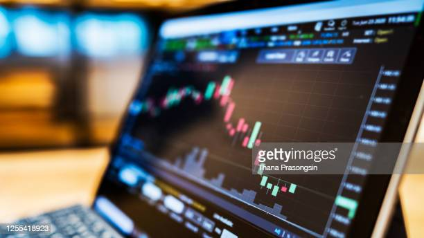 businessman using a laptop to check stock market data - performance stock pictures, royalty-free photos & images
