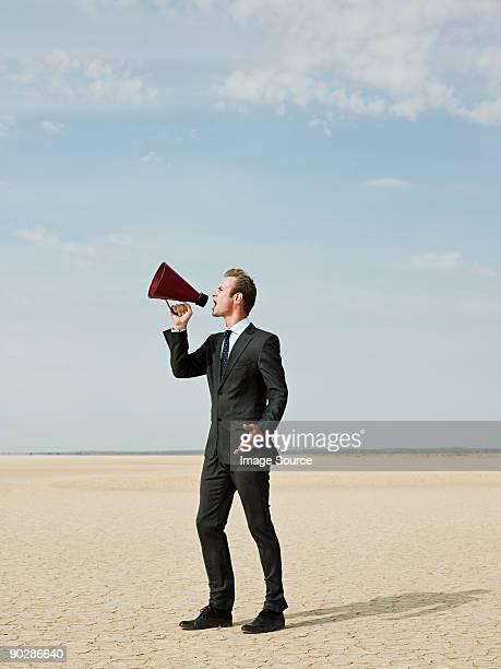 Businessman using a megaphone in the desert
