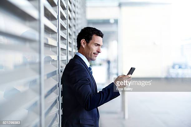 Businessman using a mobile outside a modern office