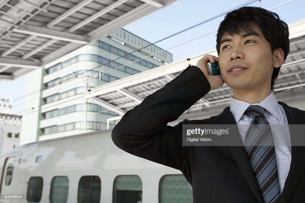 Businessman Using a Mobile Phone at a Train Station : Stock Photo
