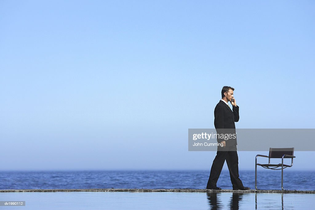 Businessman Using a Mobile Phone by the Sea : Stock Photo