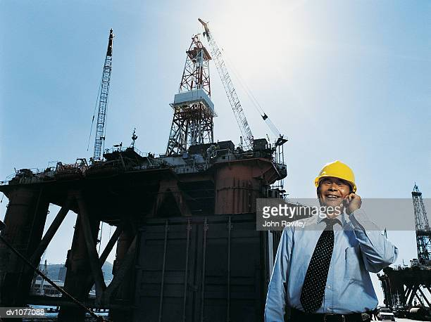 Businessman Using a Mobile Phone in a Harbour With Oil Rigs in the Background