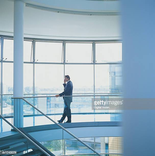 Businessman Using a Mobile Phone in an Office Lobby