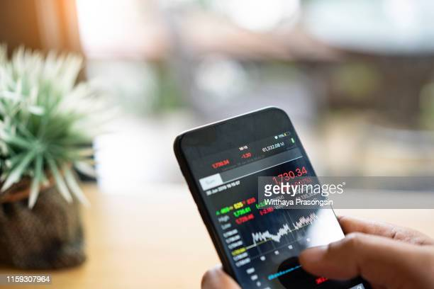 businessman using a mobile phone to check stock market data - börse stock-fotos und bilder