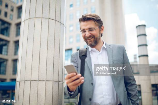 Businessman using a phone and text messaging
