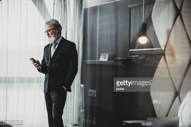Hombre de negocios usando un teléfono en la habitación del hotel