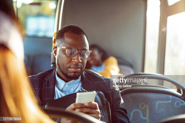 businessman using a phone while commuting on a bus - commuter stock pictures, royalty-free photos & images