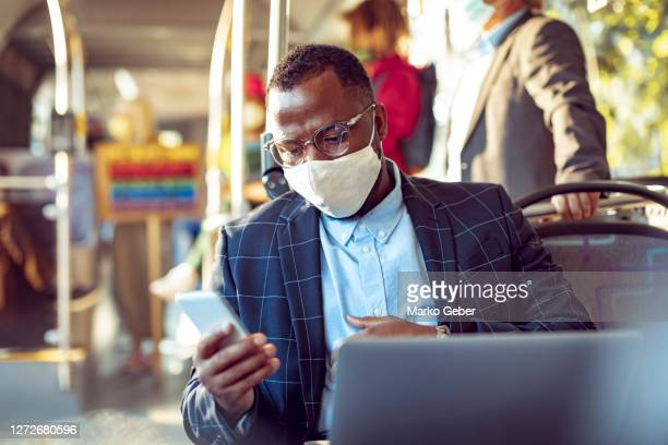 businessman using a phone while commuting on a bus - business stock pictures, royalty-free photos & images