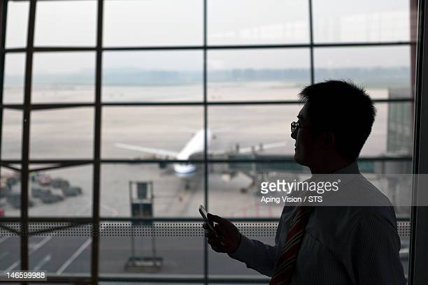 Businessman using a smart phone at an airport