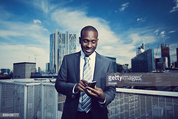 Businessman using a smart phone on the rooftop