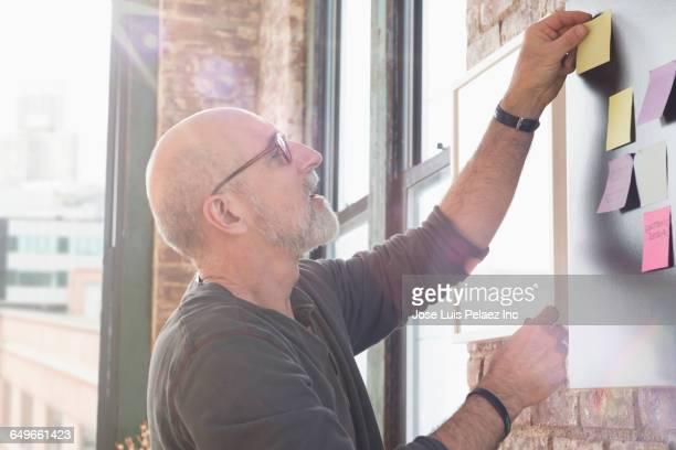 businessman using adhesive notes in office - gedächtnisstütze stock-fotos und bilder