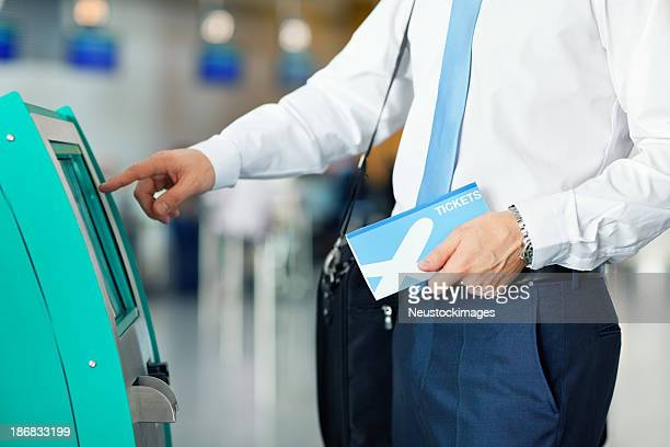 Businessman Using Automated Check In Machine At Airport