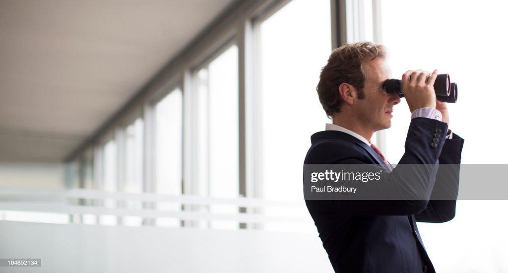 Businessman using binoculars at office window : Stock Photo