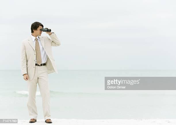 Businessman using binoculars, standing on beach