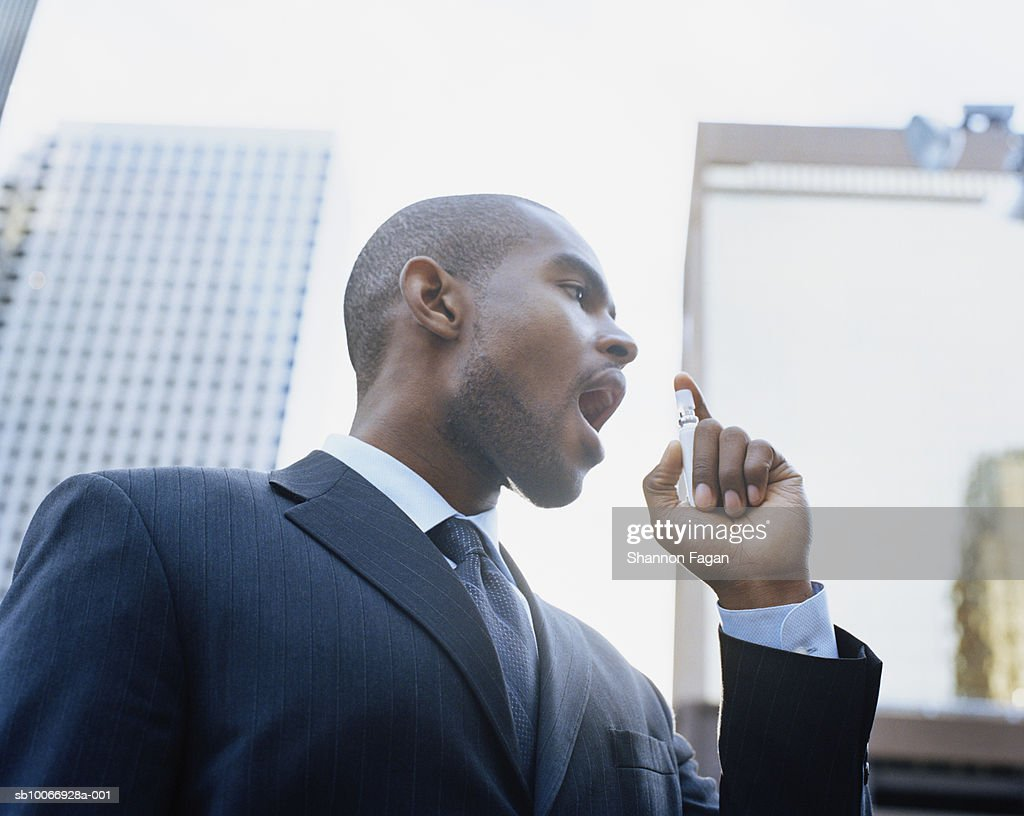 Businessman using breath freshener outdoors, low angle view : Stock Photo