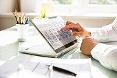 Businessman using calendar on laptop
