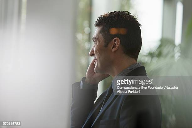 Businessman using cell phone by office window