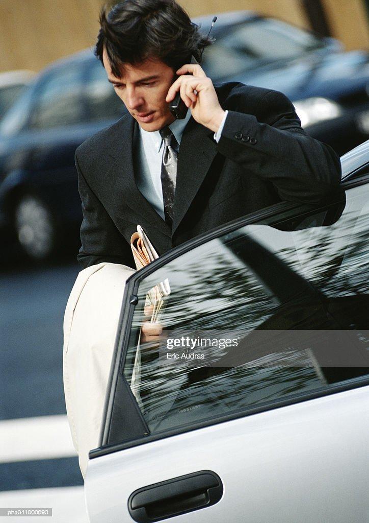 Businessman using cell phone, elbow on car door : Stockfoto
