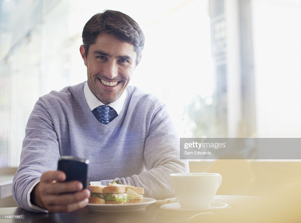 Businessman using cell phone in cafe : Stock Photo