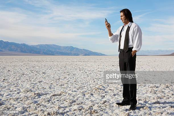 businessman using cell phone in desert - length stock pictures, royalty-free photos & images