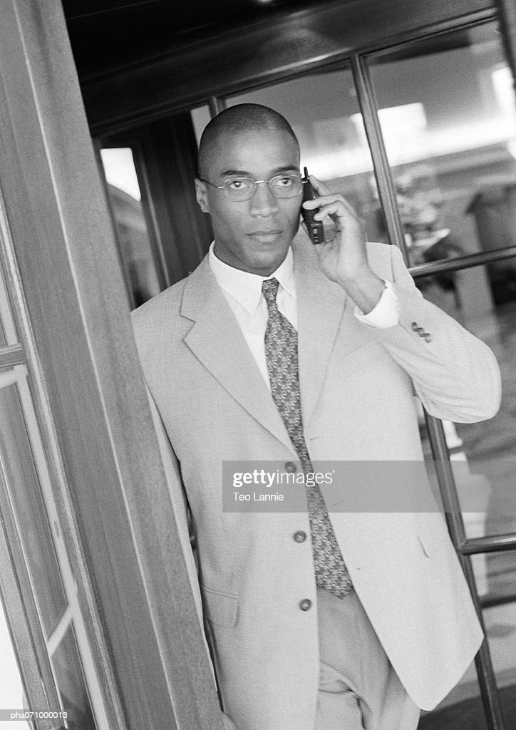 Businessman using cell phone in doorway, b&w. : Stockfoto