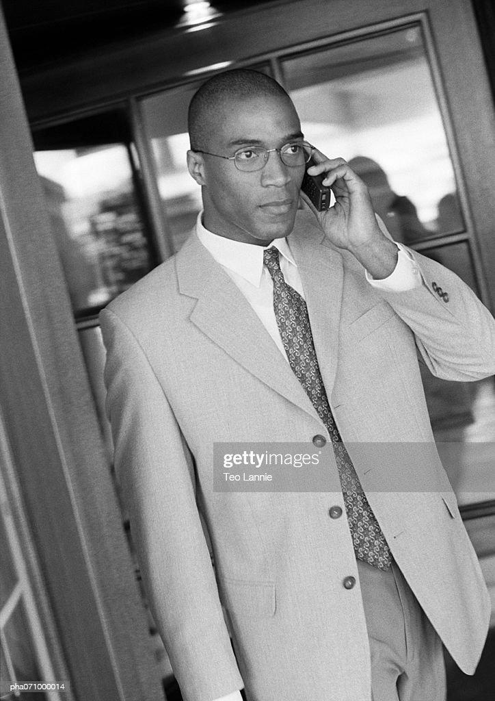 Businessman using cell phone in doorway, b&w. : Stockfoto