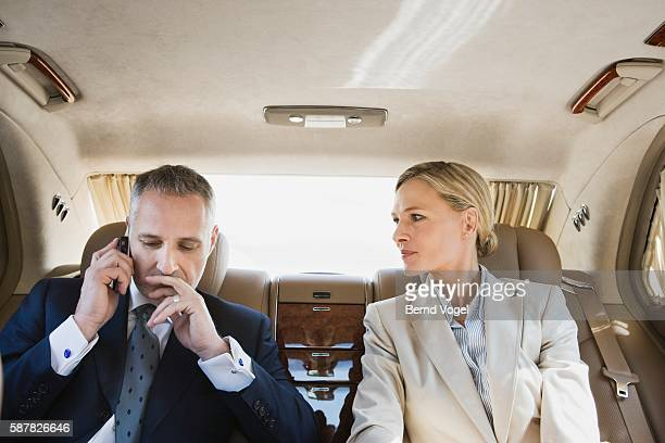 Businessman using cell phone in limousine
