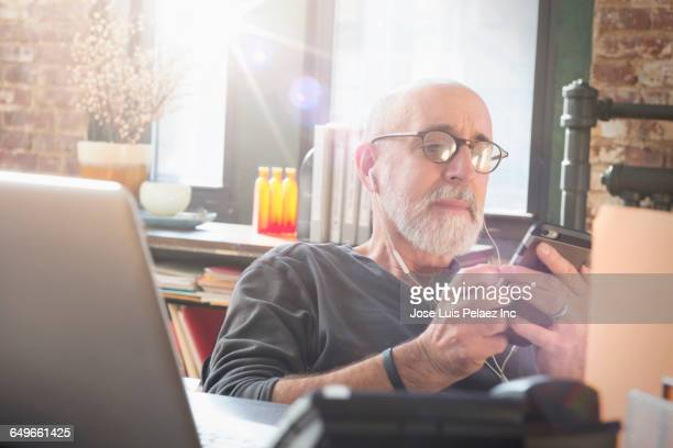 Businessman using cell phone in office