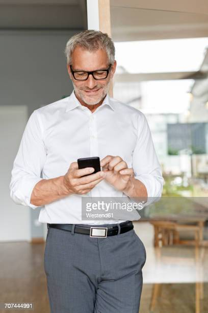 businessman using cell phone in office - three quarter front view stock pictures, royalty-free photos & images