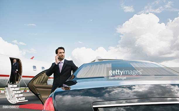 businessman using cell phone on airport runway - prosperity stock photos and pictures
