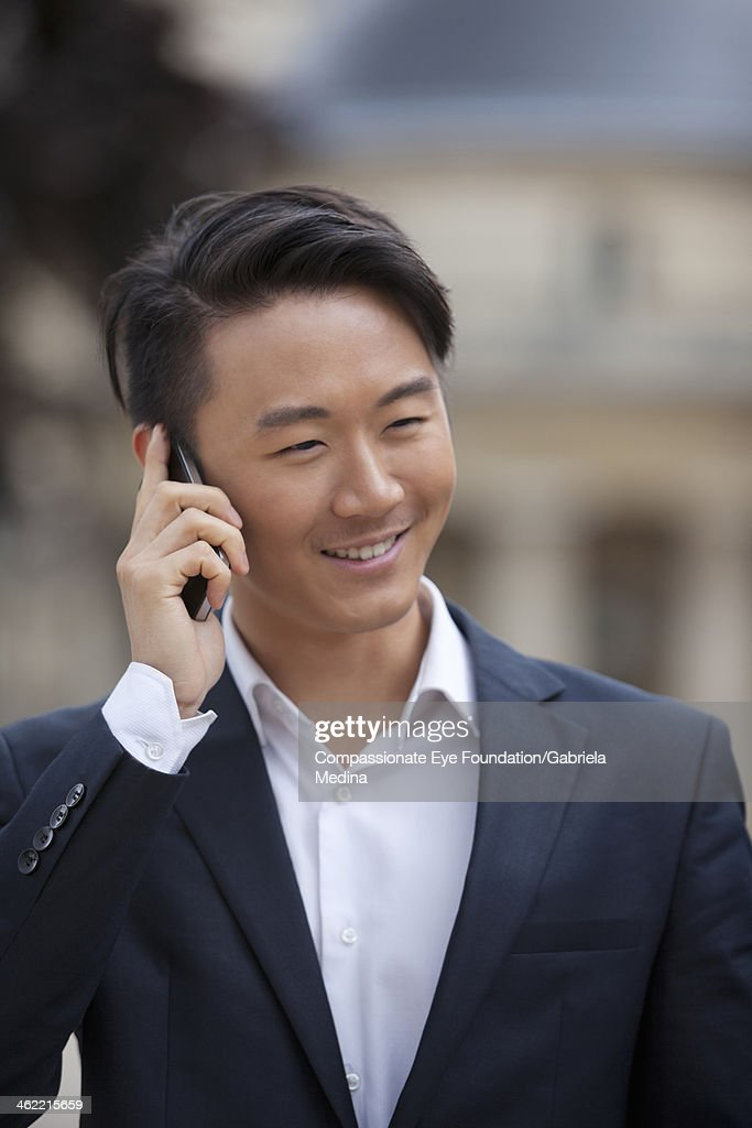 Businessman using cell phone on city street : Stock Photo