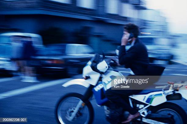 Businessman using cell phone on motorcycle in street