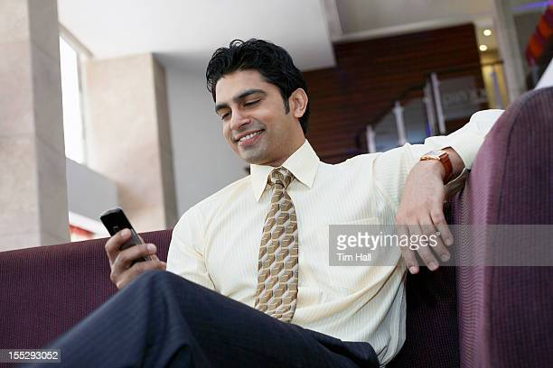 Businessman using cell phone on sofa