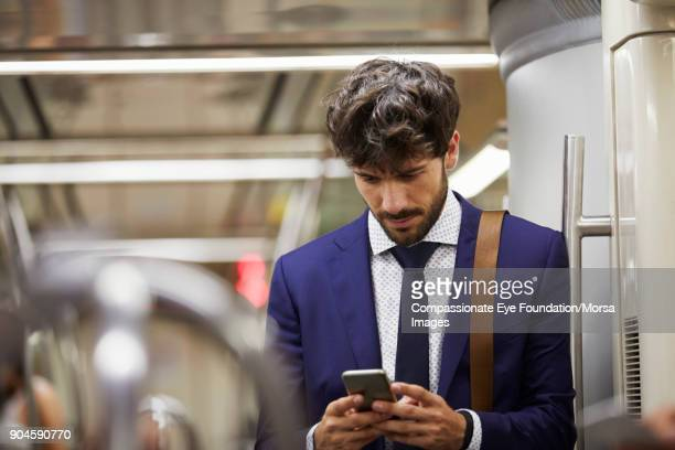 "businessman using cell phone on subway train - ""compassionate eye"" stock pictures, royalty-free photos & images"