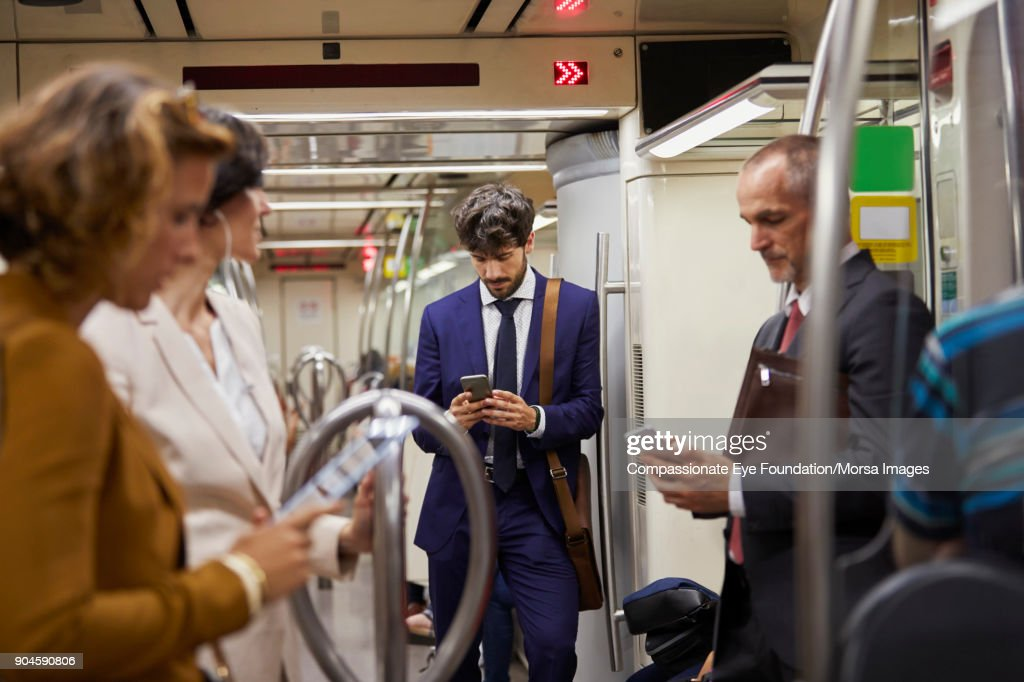 Businessman using cell phone on subway train : Stock Photo