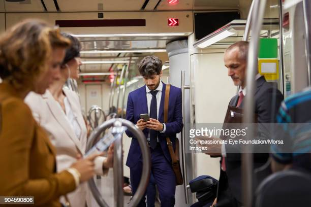 businessman using cell phone on subway train - underground stock photos and pictures