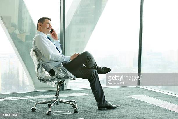 Businessman using cell phone on wrapped office chair