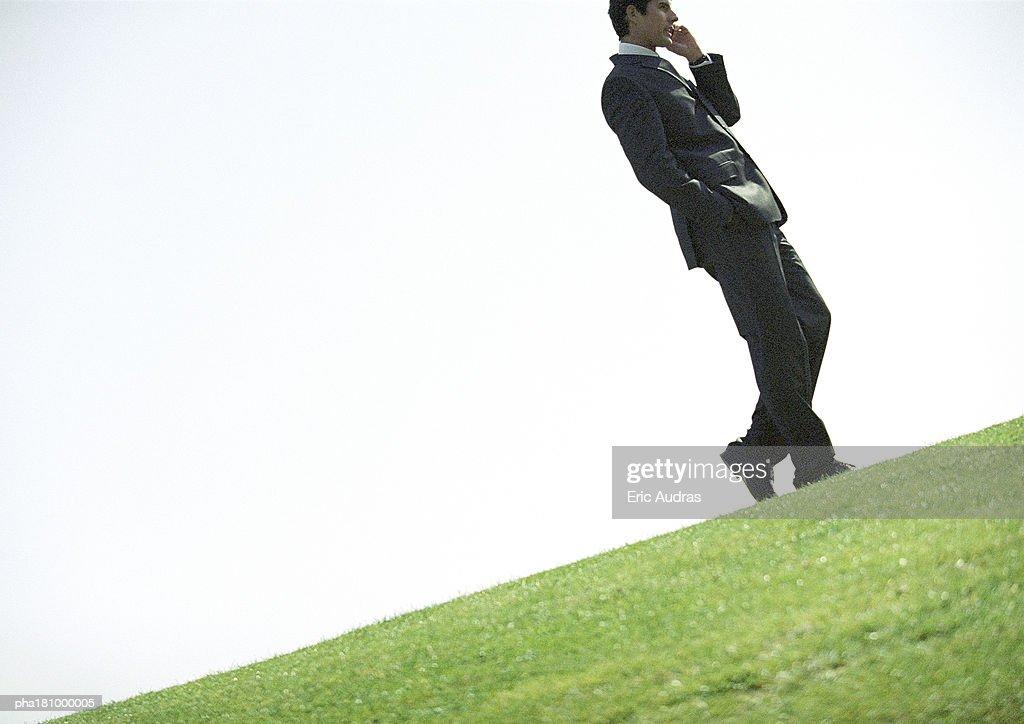 Businessman using cell phone outdoors, tilt : Stockfoto