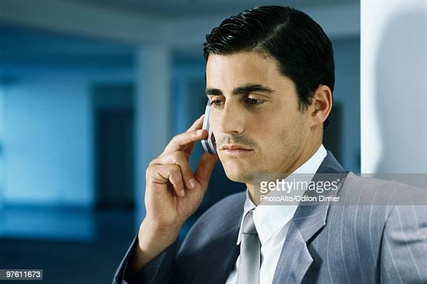 Businessman using cell phone, portrait