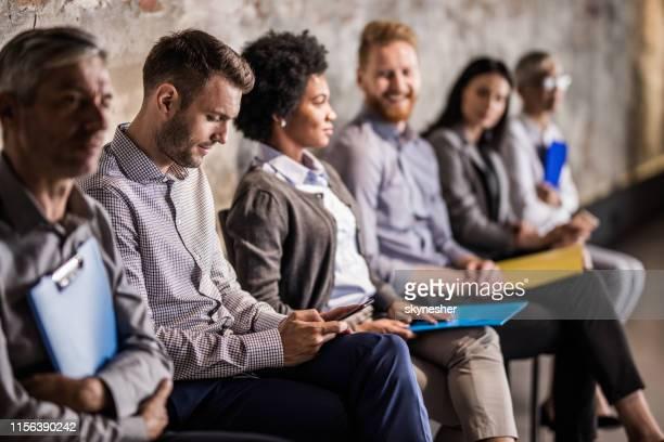 uomo d'affari che usa il cellulare in attesa di un colloquio di lavoro con altri candidati. - candidato foto e immagini stock
