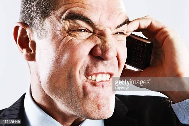 Homme d'affaires à l'aide de téléphone portable en-cas de sa Lèvre dans la frustration