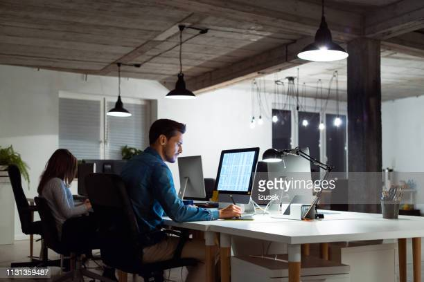 businessman using computer by female colleague - design professional stock pictures, royalty-free photos & images