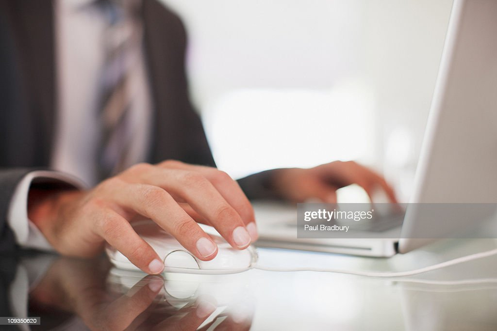 Businessman using computer mouse and typing on laptop : Stock Photo