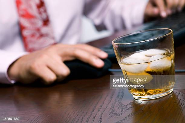 Businessman using computer next to a glass of whiskey